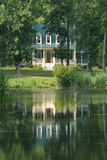 House on the water. Cottage reflecting on the water Stock Image