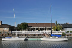 House on water with two boats in front Royalty Free Stock Photography