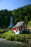 House and waterfall. Traditional norwagian wooden house and waterfall in the distance Royalty Free Stock Image