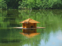 House for waterfowl. On the pond among green trees Royalty Free Stock Photo