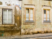 Weathered facade with yellow azulejos in Portugal. A house with weathered yellow azulejos ceramics in Portugal stock photos