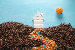 The house from white chocolate, the earth from coffee grains, the road from almonds, the sun from a citrus on blue Stock Images