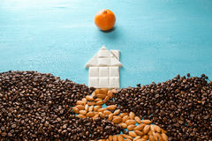 The house from white chocolate, the earth from coffee grains, the road from almonds, the sun from a citrus on blue. Background. Abstract symbols flat lay royalty free stock image