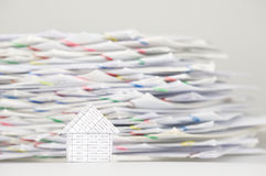 House on white table have blur stack overload of paperwork. With colorful paperclip as background Stock Photography