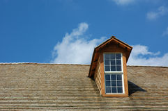 House Window. Home window with bright blue sky background and cedar tile roof royalty free stock image