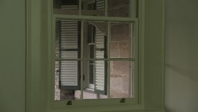 A house window shot. A medium shot of a house window. Camera zooms in and out stock video footage