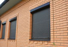 House Windows with rolling shutters for home protection. Brick House Windows with rolling shutters for home protection stock photography