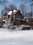 House in Winter. The Side View of A Beautiful and Colorful Historic House with Pine trees in Winter time royalty free stock photo