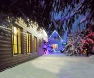 House in the winter forest, bright festive color garlands light the area, snow on royalty free stock photos