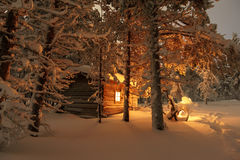 House in the winter forest. Cabin in Snow Covered Forest Stock Photos