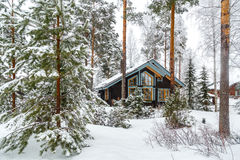 House in the winter forest. Cabin in Snow Covered Forest Stock Photography