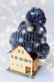 House in winter - heating system concept and cold snowy weather. With model of a house with warm protection / insulation stock image