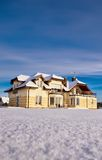 House in winter. Scenic view of a large countryside house with a snow covered field in the foreground, winter scene Stock Photos