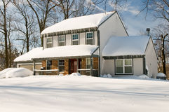 House after winter snowstorm. Suburban house and front yard with cars covered by drifted snow after a heavy winter snowstorm Royalty Free Stock Photo