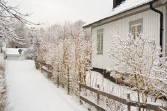 House at a winter walking path. Snow covered walking path at a white house Stock Photo