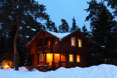 House in winter wood in twilight. Wooden house in winter wood in twilight royalty free stock images