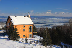 House in Wintry landscape. Exterior of luxurious house in Wintry countryside overlooking Saint Lawrence river, Charlevoix, Quebec, Canada Royalty Free Stock Photos