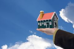 House in woman hand and sky. Miniature house in woman hand held against blue skies - real estate concept stock photo