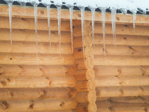 House of wood in winter with icicles. Royalty Free Stock Photos