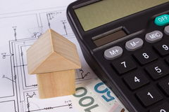 House of wooden blocks and polish money with calculator on construction drawing, building house concept Stock Image