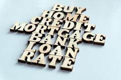 House of wooden letters. The words BUY, HOME, CREDIT, MORTGAGE, BANK, LOAN, RATE are laid on a white background. Concept of mortga