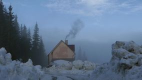 House in the woods in the mountains. The chimney's smoke. The action in real time stock footage