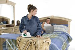 House work-business work. Young couple with woman ironing clothes and man working on laptop-metaphor for successfully blending family and business stock photography