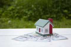 The house is worth a hundred dollar bills. Conceptual photo stock images