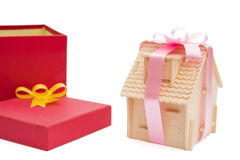 House wrapped with ribbon besides a present box Royalty Free Stock Photo