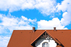 House wuth red roof under blue cloudy sky Royalty Free Stock Photography