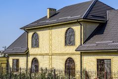 House of yellow brick and brown corrugated roof made of metal. Lattices on the windows. Royalty Free Stock Photo