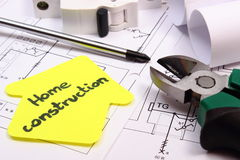 House of yellow paper, work tools, electric fuse and construction drawing Stock Photos