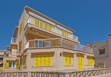 House with yellow window shutters Royalty Free Stock Images