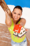 This house is for you!. Attractive woman worker at the ladder offering a  miniature house to us, focus on the woman Stock Photo