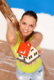House for you. Attractive woman worker at the ladder offering a  miniature house to us, focus on the house Stock Images