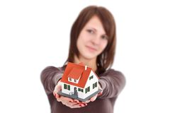 House for you. Lovely woman offering a miniature house, symbol of a new home Stock Photo
