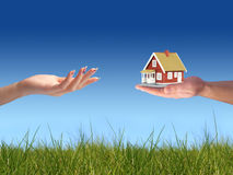 House for you. Concept of home ownership. Hand giving new house Stock Image
