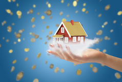 House for you. Concept of home ownership. Hand giving new house. Coins on the background Stock Photos