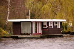 Houseboat. A wooden houseboat in the county and a garden with a weeping willow and a birch Royalty Free Stock Images