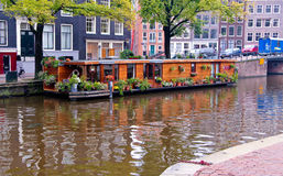 Houseboat in Amsterdam canal. Precious wooden houseboat with flowers and plants in one canal of Amsterdam Royalty Free Stock Photos