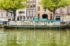 Houseboat in Amsterdam canal. Ancient wooden houseboat closed in one canal of Amsterdam Royalty Free Stock Images