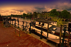 Houseboat and Bicycles in Amsterdam. Urban scene in Amsterdam with houseboat and many bicycles at sunset. Street View with bikes parked on an embankment in the Royalty Free Stock Image