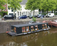 Houseboat in canal. Floating houseboat in a canal in Groningen, Netherlands Stock Photo
