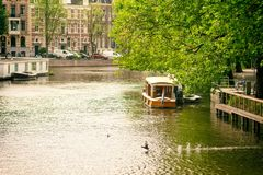 Houseboat at daytime, Amsterdam canal - Holland Netherlands. Houseboat daytime Amsterdam canal - Holland Netherlands Royalty Free Stock Photo