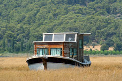 Houseboat in rushy shallow waters of bay Stock Photography