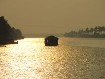 A houseboat sailing during sunset at Alleppy Backwaters, Kerala, India stock photos