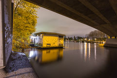 Houseboat situated under a bridge in the Amstel river in Amsterdam Royalty Free Stock Photos
