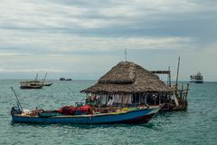 Houseboat and small boats near the ocean stock photos
