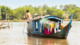 Houseboat with young man paddling, Vietnam. Stock Photography