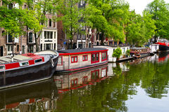 Houseboats on Amsterdam canal. Characteristic view of an Amsterdam, the Netherlands, canal with house boats on a Spring morning: Brouwersgracht and Mouthaansteeg Royalty Free Stock Photo